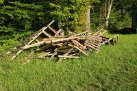 Holzstapel aus alten Hochsitzen am Waldrand