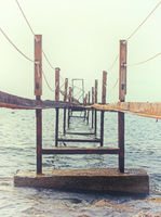 a perspective view of a broken rusty iron jetty running into to sea on a sunlit misty morning