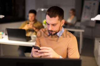 man with smartphone working late at night office