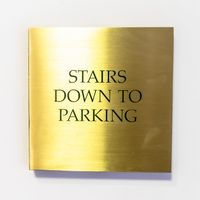 Square Gold plated sign that reads Stairs Down To Parking against white interior wall