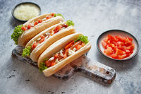Three barbecue grilled hot dogs with sausage placed on wooden cutting board