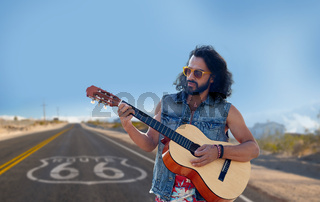 man playing guitar over us route 66 background