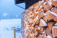 firewood with snow side view by a hut