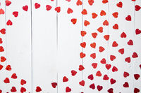 Vlentine's Day composition. Heart shaped sequins placed on white wooden table
