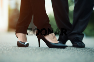 Closeup of businessman's and businesswoman's legs outside