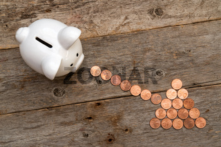 Piggy bank and coins arranged as a arrow