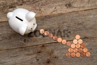 Piggy bank and coins arranged as a arrow