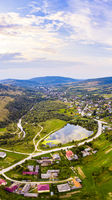 Vertical landscape of settlement in valley between mountains. Sunset time, end of summer. Aerial drone view of urban village Pidbuzh in Carpathians, Ukraine