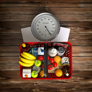 Groceries in a shopping basket on weight scale. Overnutrition, malnutrition, overconsumption and diet concept.
