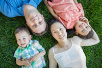 Chinese Mother, Caucasian Father and Mixed Race Children Laying On Grass