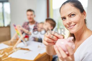 Frau mit einem Sparschwein und Geldmünze