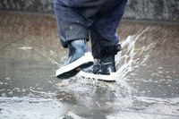 Close-up of kid wearing blue rain boots and walking during sleet, rain and snow on cold day