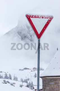 Snowy sign giving way