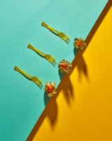 Flat lay view of the pattern of three yellow physalis fruit and forks with shadows on diagonally duotone yellow green background