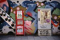 Zeitungsständer und Elektroverteilerkasten vor Graffitiwand