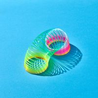 Toy plastic rainbow slinky with shadows on blue.