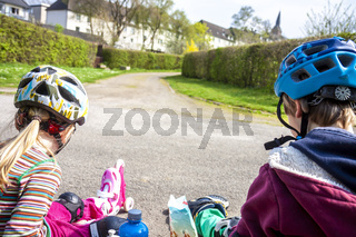 Boy and girl wearing roller-blades sitting and eating and drinking mineral water