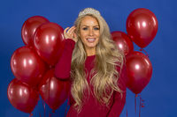 Lovely Blonde Model Posing In A Dress And Tiara Against Red Balloons In A Studio Environment