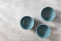 Three blue hand crafted chinese bowls on gray stone background. Flat lay