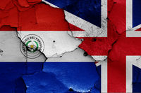 flags of Paraguay and UK painted on cracked wall