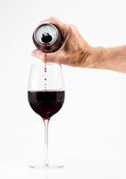 Senior adult pouring a glass of red wine from an aluminum can