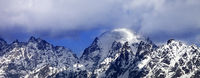 Panoramic view on snowy mountains in clouds