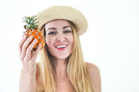 Pretty young woman in swimsuit and straw hat holding fresh pineapple