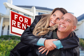 Happy Couple Hugging in Front of For Rent Real Estate Sign and House
