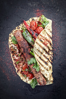 Traditional Adana Kebap with tomato and salad on a flatbread with copy space