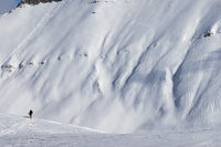 Skiers and off-piste slope with traces of skis, snowboards and avalanches