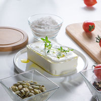 In a white plate cheese with greens, peeled sunflower seeds and tomatoes on an unused kitchen table