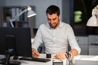 businessman using smart speaker at night office