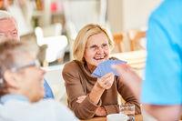 Senior Frau hat viel Spaß beim Karten spielen