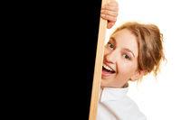 Lachende Frau hinter schwarzer Tafel