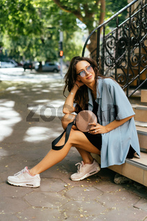 Beautiful young girl sitting on the steps outside