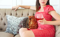 Young woman with a glass of wine sitting on the sofa in red dress