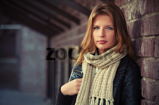 Young fashion girl in leather jacket and knitted scarf