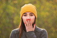 Young woman covering her mouth with her hand.