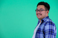 Profile view of happy young overweight Asian hipster man smiling