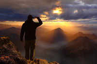 Young male hiker standing on the peak of the mountain