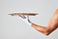 Waiter with muscular hand in a white glove holding a metal empty tray on a white background