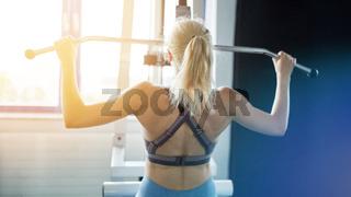 Rücken einer Frau bei Rückentraining am Latzug