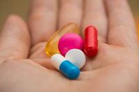 multiple colors pills in young hand , Taking Your Medication.