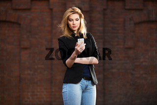 Young fashion blond business woman using smart phone on city street