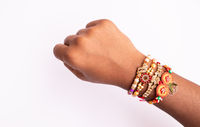 Indian festival Raksha Bandhan, raki or Raakhi on hand on isolated background