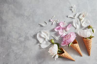 Creative composition from delicate flowers in a wafer cones with petals on a gray stone table. Flat lay