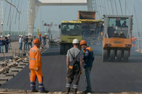 The construction of the Crimean bridge. Asphalt paving. Road works on the bridge.