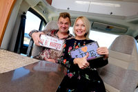 Cheerful middle age married positive travelers couple sitting inside of camper holds showing hippy retro styled number plate or license number with text This the season to be married and I love life