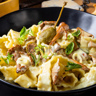 Reginette noodles in cream sauce with fresh chanterelles and capers