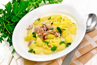 Soup creamy of chicken and pasta in plate on kitchen towel
